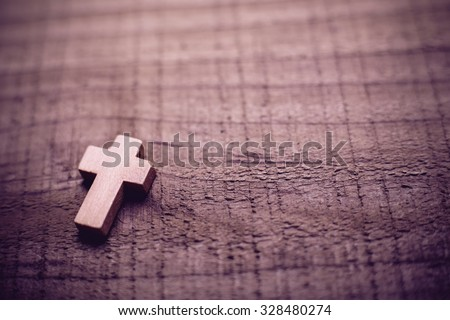 Wooden cross lying on the rustic wooden background. - stock photo