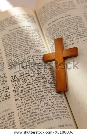 wooden cross on a old bible with the light from window - stock photo
