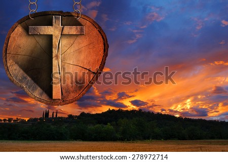 Wooden Cross on Tree Trunk at the Sunset. Wooden Christian cross on a section of tree trunk, hanging from a metal chain at the beautiful sunset over the hills with clouds - stock photo