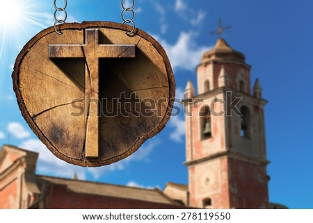 Wooden Cross on Tree Trunk with Church / Wooden Christian cross on a section of tree trunk, hanging from a metal chain. In the background, an blurred ancient church with bell tower - stock photo