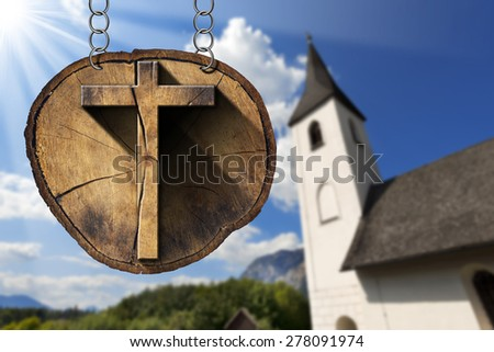 Wooden Cross on Tree Trunk with Small Church / Wooden Christian cross on a section of tree trunk, hanging from a metal chain. In the background a small mountain church - stock photo