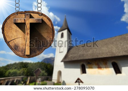 Wooden Cross on Tree Trunk with Small Church / Wooden Christian cross on a section of tree trunk, hanging from a metal chain. In the background a small blurred mountain church - stock photo