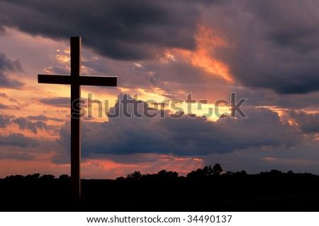 Wooden cross over a sunset