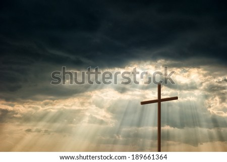 Wooden cross stand against a dramatic evening sky with radiant beams penetrating clouds - stock photo