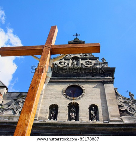 wooden cross with crucifix closeup on background Church of St. Andrew against blue sky