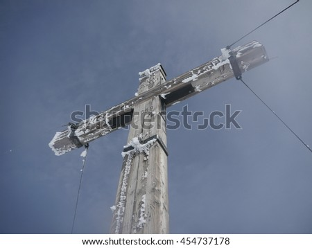 Wooden cross with metal hawsers  - stock photo