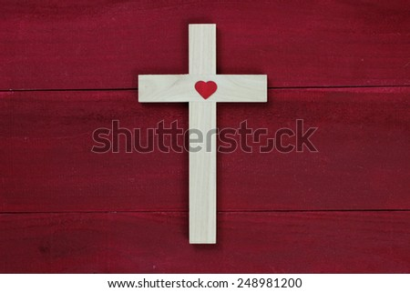Wooden cross with red heart on antique red wood background - stock photo