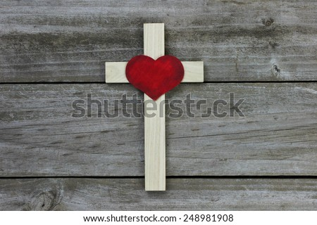 Wooden cross with red heart on rugged wood background - stock photo