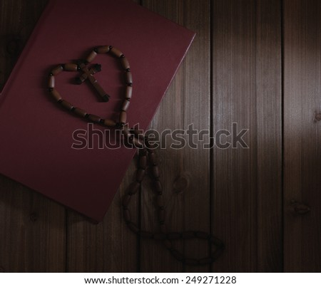 wooden cross with rosary lies in the holy book of the Bible - stock photo