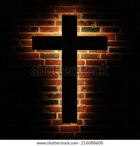 Wooden cross with the light on the brick wall - stock photo
