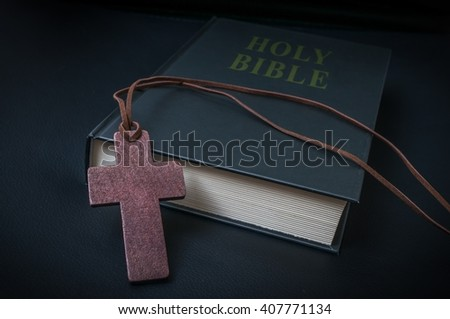 Wooden crucifix on necklace and Holy Bible. - stock photo