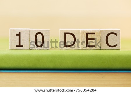 Wooden cube shape calendar for DEC 10 on green book, table.