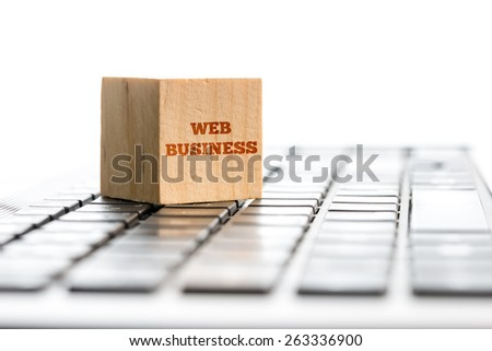 Wooden cube with a Web business sign sitting on computer keyboard. Conceptual of modern globalization and online business. - stock photo