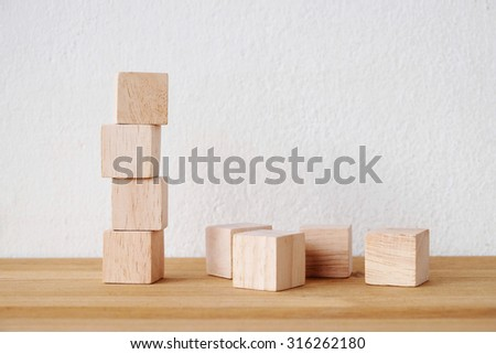 Wooden cubes on table over cement wall background - stock photo