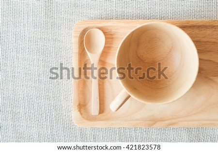 Wooden cup and spoon with saucer on grey textile - stock photo