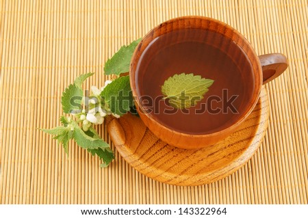 Wooden cup of nettle tea on bamboo mat - stock photo