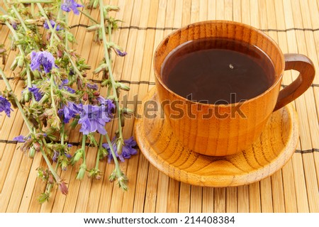 Wooden cup of tea with chicory on bamboo background