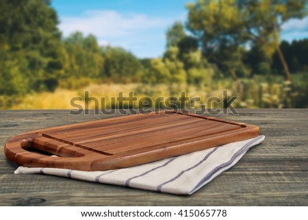 Wooden Cutting Board Close-up On The Picnic Table And Summer Landscape In Blurred Perspective - stock photo