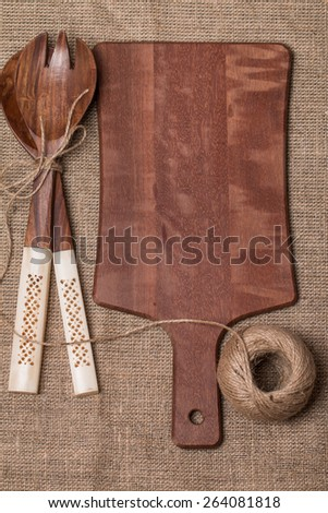 wooden cutting board, spoon and fork  for salad on burlap, concept, place for the recipe, top view - stock photo