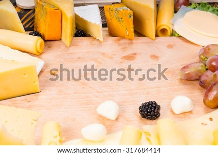 Wooden Cutting Board Surrounded by Variety of Gourmet Cheeses and Fresh Fruit with Copy Space in Center of Image - stock photo