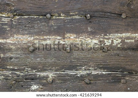 Wooden dark background with old rusty nails. Rough and faded tones. - stock photo