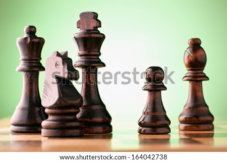 Wooden dark chess pieces on a chessboard against a green background with a king, queen, bishop, knight and pawn - stock photo