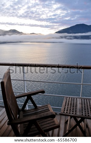 wooden deck chair and table on cruise ship in scenic alaskan passage at dawn - stock photo