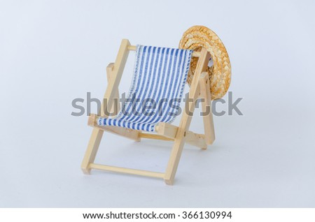 Wooden deck chair with sun hat on a white background. - stock photo