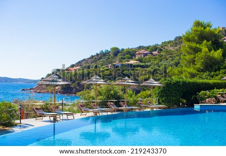 Wooden deck chairs near infinity pool in luxury resort - stock photo