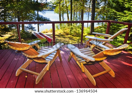 Wooden deck of cottage with Adirondack chairs at lake - stock photo