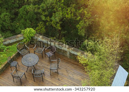 Wooden deck surrounded by trees with seating arrangement with steel metal framed table and chairs by look down.