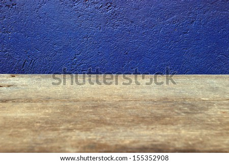 Wooden deck table on blue grunge background - stock photo