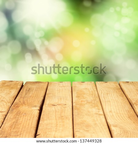 Wooden deck table over beautiful bokeh background - stock photo