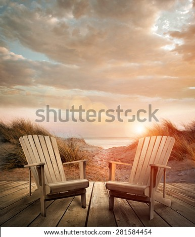 Wooden deck with chairs, sand dunes and ocean in background - stock photo