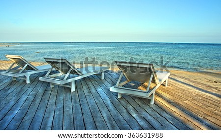 wooden deck with chairs to relax by the beach with a spectacular view over the ocean - stock photo