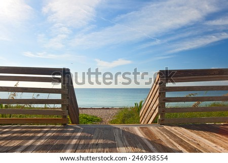 Wooden deck with fence overlooking the ocean and the beach in the famous tourist destination of Key West in Florida Keys - stock photo