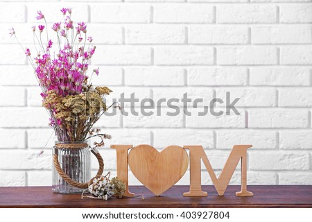 Wooden decor and flowers for mother's day on brick wall background - stock photo