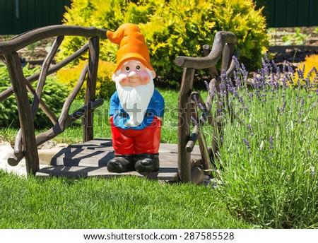 Wooden decorative bridge with garden dwarf  in home garden. - stock photo
