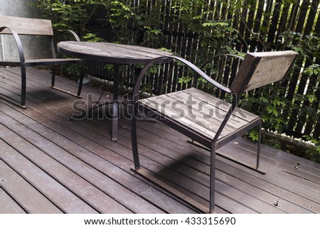 wooden desk and chair on patio beside garden