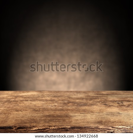 wooden desk and dark wall - stock photo