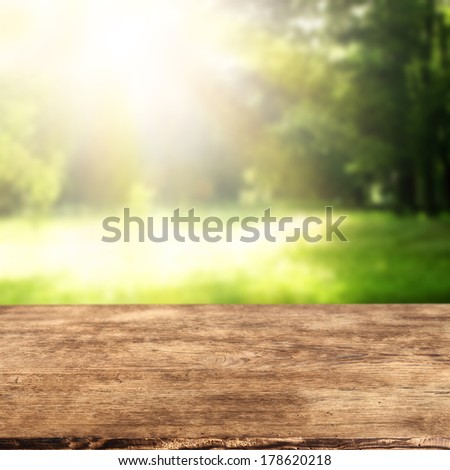 wooden desk and garden background with empty space  - stock photo