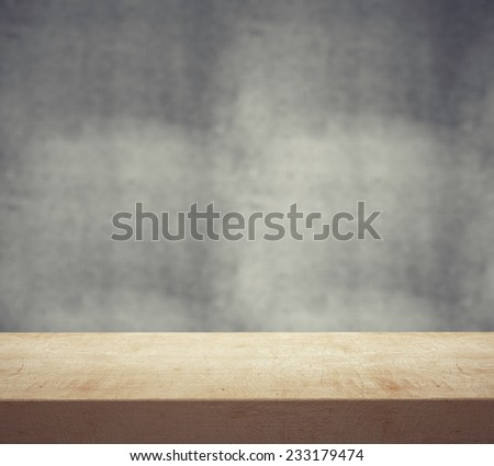 wooden desk and gray wall, close up - stock photo
