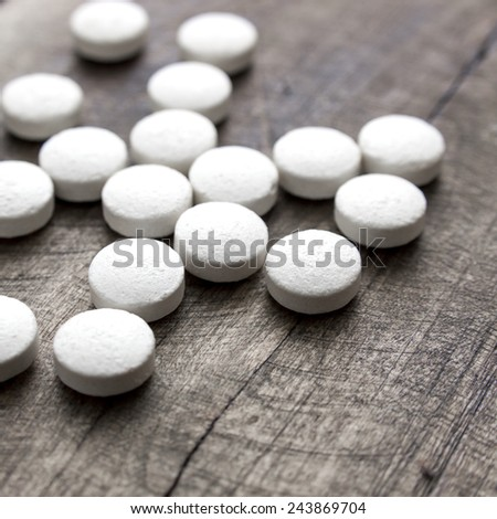 wooden desk and pills, close up photo - stock photo