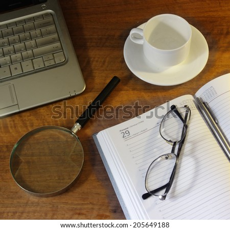 Wooden desk with an appointments diary, pen, glasses, magnifying glass and a coffee cup on it - stock photo