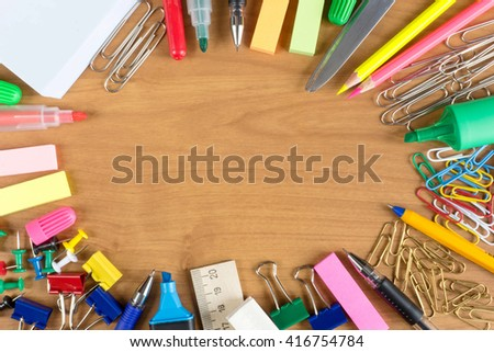 Wooden desk with lots of stationery objects - stock photo