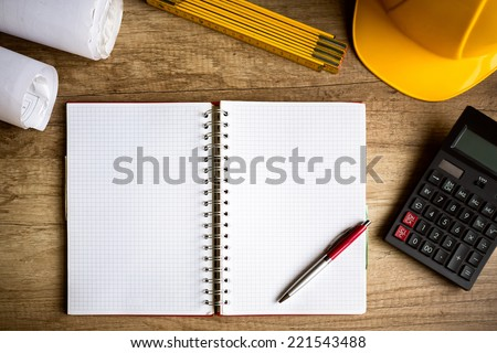 wooden desk with open notebook, blueprint rolled, hamlet, calculator - stock photo