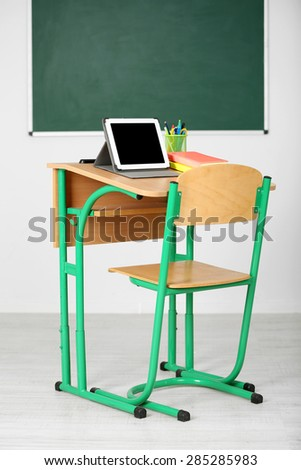 Wooden desk with stationery and tablet in class on blackboard background