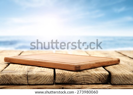 wooden desk wooden table and blue sea  - stock photo