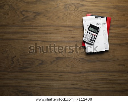 wooden desktop with calculator and invoices - stock photo