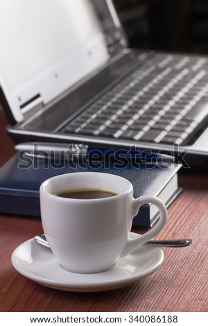 Wooden desktop with morning coffee cup, opened laptop computer, diary and pen on background, no people, focused on coffee